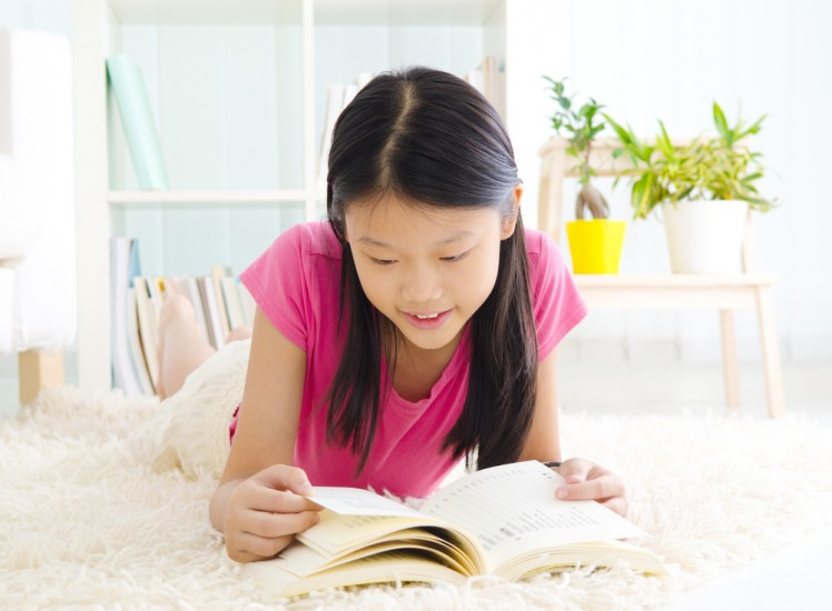 image of girl reading on carpet for header image for residential carpet cleaning service from carpet cleaning authority